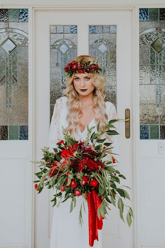 a lush red and green wedding bouquet with red ribbons and a matching floral crown
