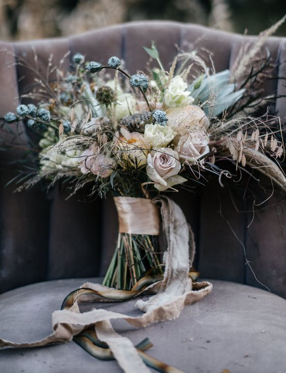 a neutral boho winter wedding bouquet with herbs, blush roses, white blooms and dusty pink ribbons