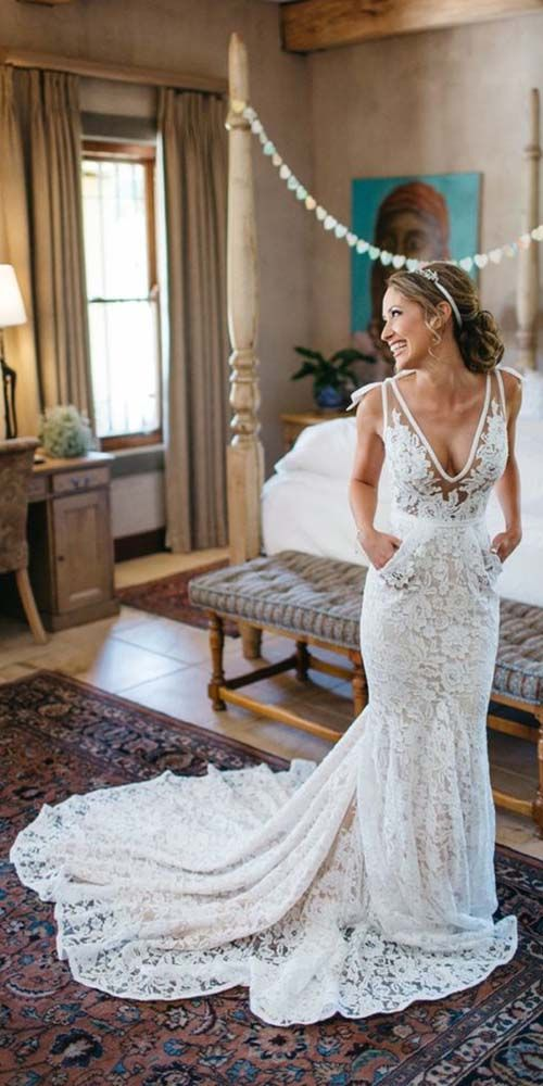 a sleeveless wide strap mermaid wedding dress with a train and a plunging neckline