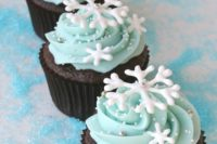 12 chocolate cupcakes with ice blue frosting, silver beads and snowflakes for a winter wedding