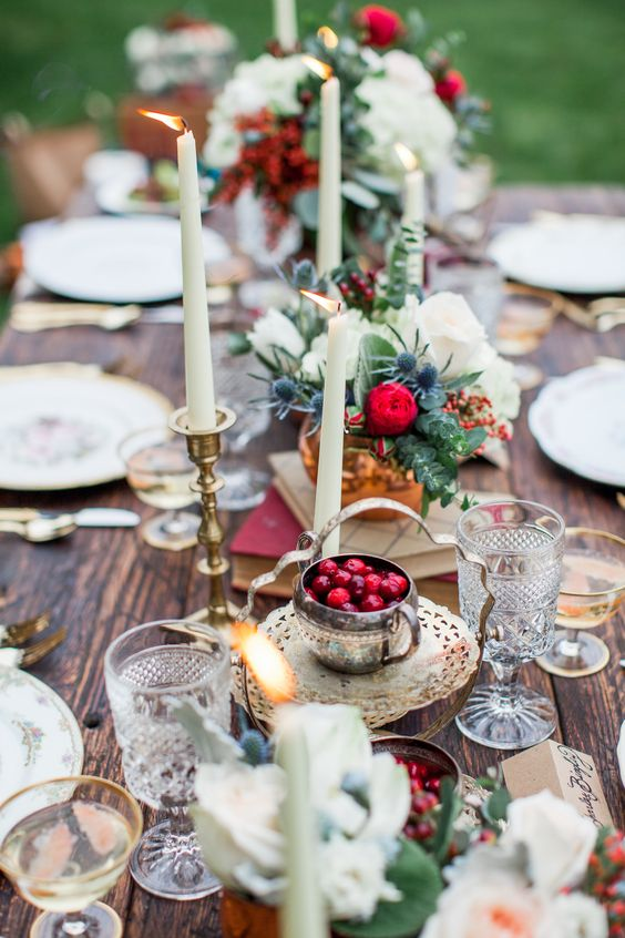 a boho tablescape with copper and gold accessories, crystal glasses, cranberries, thistles and eucalyptus and candles