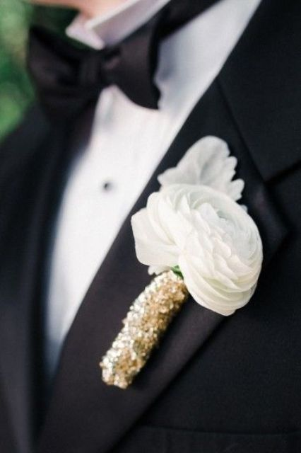 a buttonhole with white ranunculus and gold sequin wrap for a touch of sparkle