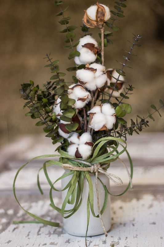 a cool arrangement with eucalyptus, cotton and grass in a mason jar for a cozy relaxed wedding