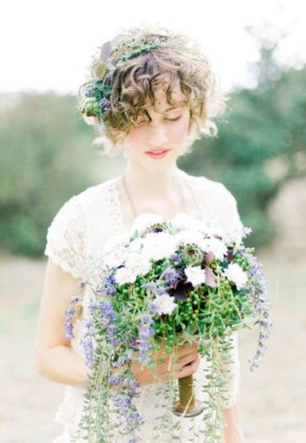 a curly hairstyle with a fresh greenery and purple bloom crown and a matching bouquet
