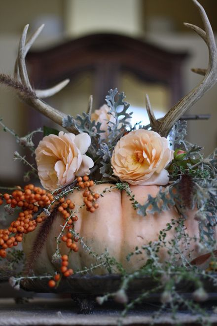 a cute fall wedding centerpiece with foliage, berries, pastel blooms and antlers