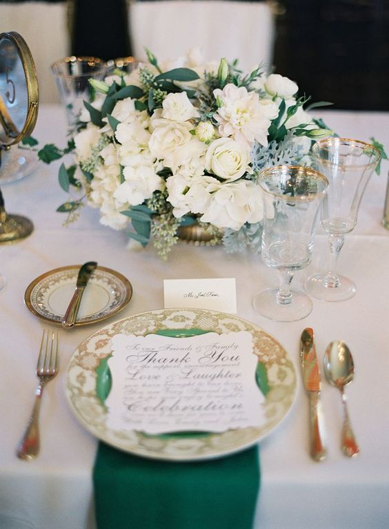 a glam table setting in emerald and gold, with a lush floral centerpiece and emerald linens