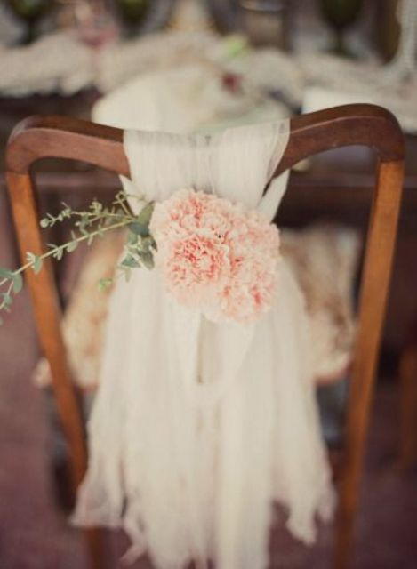 a layered tulle chair cover with peachy blooms and a touche of greenery for a rustic wedding