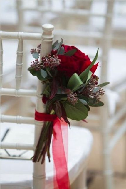 decorate the aisle with greenery and crimson roses with ribbons