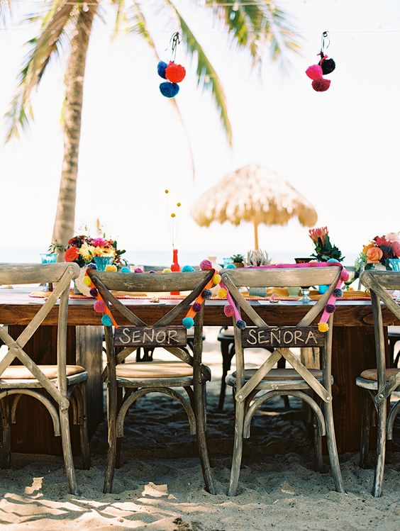 reclaimed Senor and Senora wedding chair signs and colorful pompom garlands for Mexican weddings