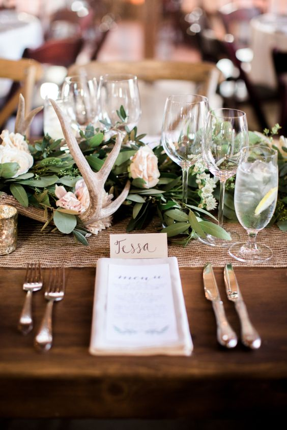 a foliage wedding table runner, pastel blooms, antlers and candles for an elegant rustic wedding