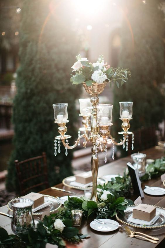 a gorgeous glam tablescape with vintage candle holders, liush foliage and white blooms