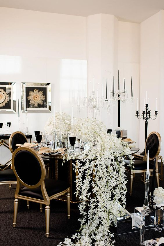 a gorgeous black and gold wedding tablescape with a lush white bloom runner and black chairs for a match