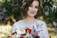 15 a messy wavy hairstyle accessorized with a fresh flroal headband of white, red blooms and greenery