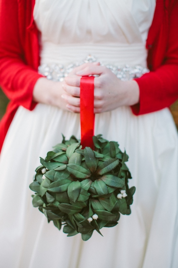 a unique topiary bouquet on a red ribbon handle is a creative idea for a winter bride