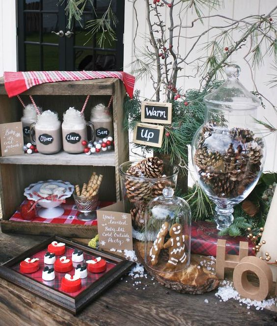 a cozy hot chocolate bar with evergrens, faux snow, pinecones and various desserts to choose from