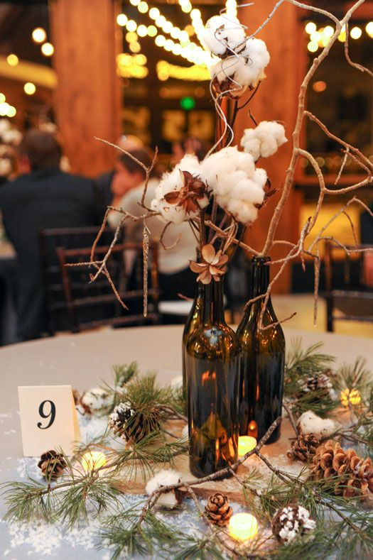 a cozy winter centerpiece with snowy pinecones, evergreens, candles, cottons and wine bottles with branches