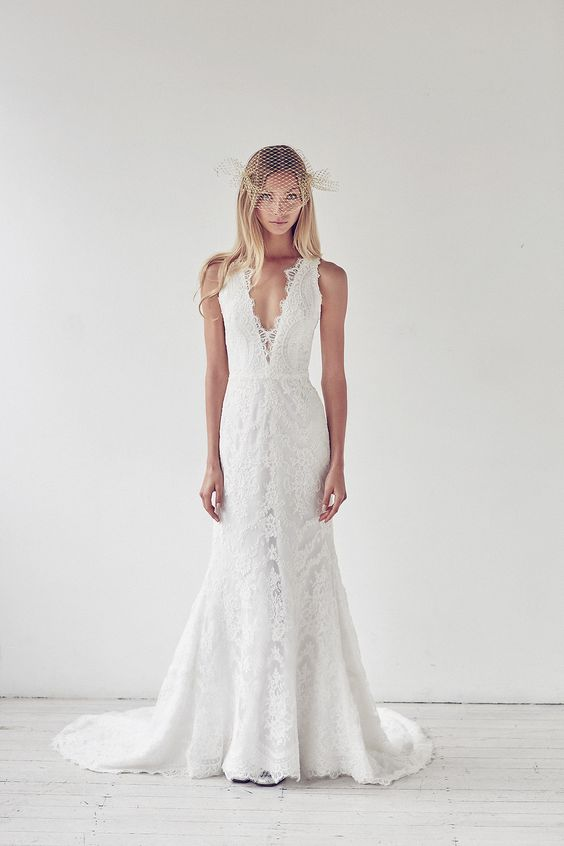 a lace plunging neckline wedding dress with a small train and a lace edge