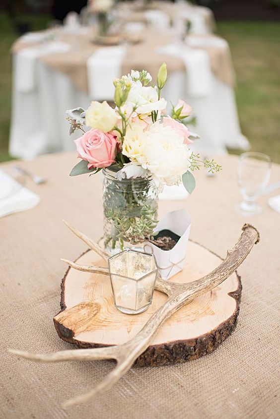 a rustic centerpiece with antlers, a candle holder, pastel and neutral blooms