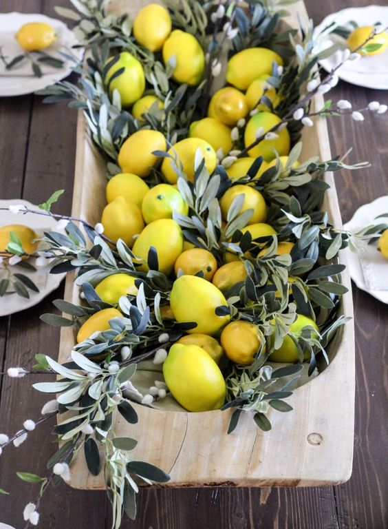 a wooden dough bowl with pussy willow and lemons for a Tuscany inspired wedding