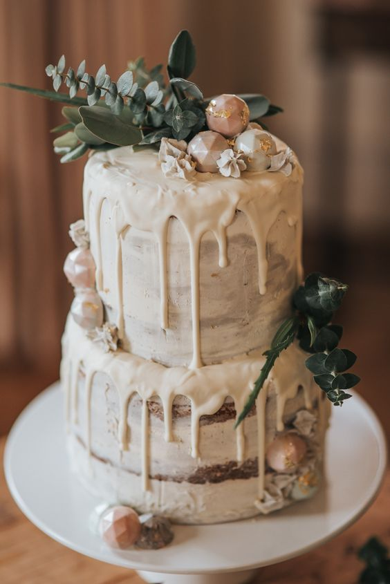 neutral semi naked wedding cake with white chocolate dripping, eucalyptus and pastel geometric candies with gold leaf