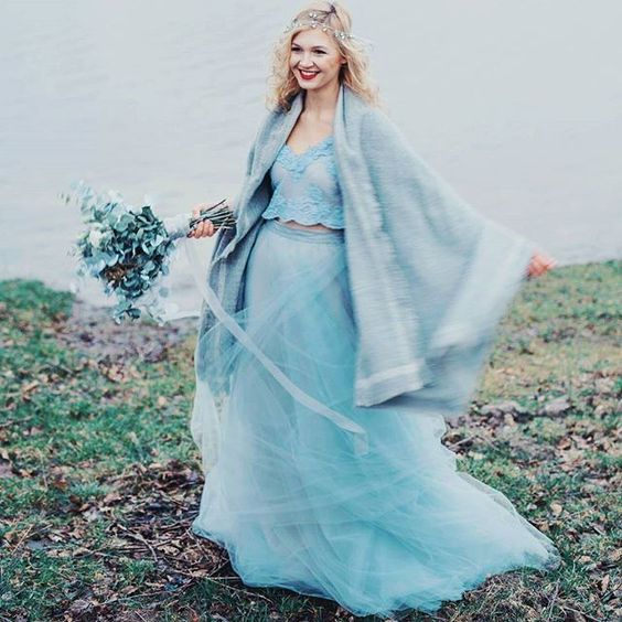 the bride wearing an ice blue separate with a lace crop top, a layered tulle skirt, a comfy coverup and an icy blue bouquet