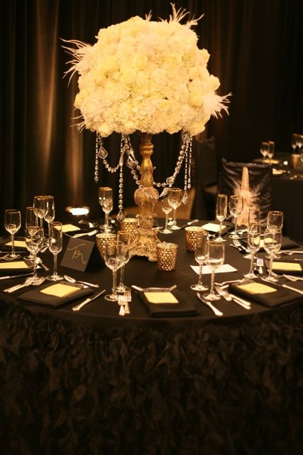 a black tablecloth with ruffles, a white bloom and feather centerpiece with hanging crystals and candles holders