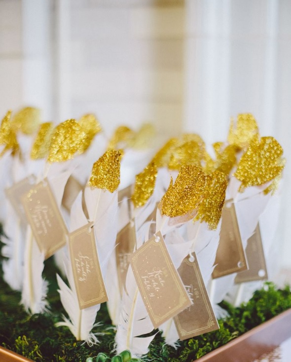 a feather escort card display with gold glitter looks bold for any wedding
