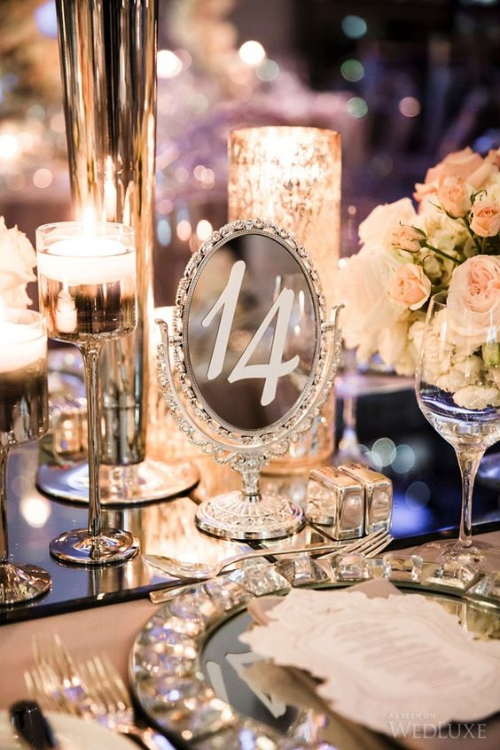 a glam winter wedding tablescape with candles, sparkling chargers and mirror table numbers