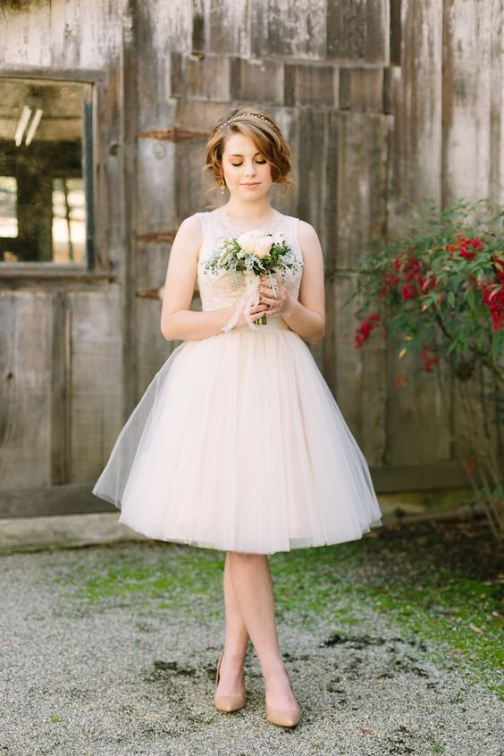 a gorgeous and cute wedding dress with a scoop neckline, wide straps, no sleeves and a full layered skirt