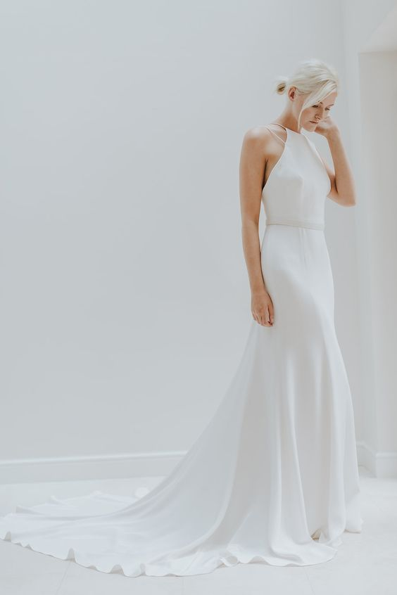 a modern halter neckline wedding dress with straps and a train looks very chic