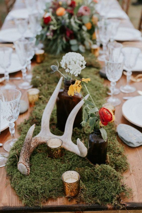 a moss table runner with candles, wildflowers in bottles and antlers for a woodland-inspired wedding