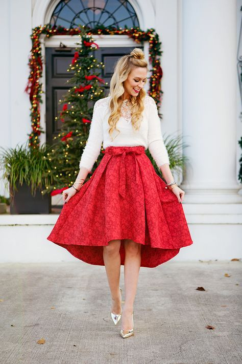 a red high low printed skirt with a bow, a white sweater and a statement necklace with silver shoes
