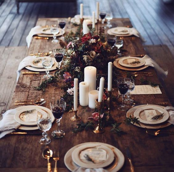 a rustic boho winter wedding tablescape with candles, dark florals and foliage and refined plates and cutlery
