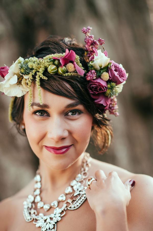 a short wavy hairstyle with a lush floral crown with fuchsia blooms, white flowers and greenery and a matching lipstick