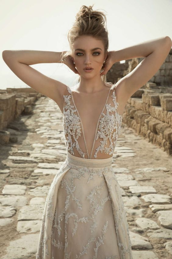 a stunning beaded and embroidered wedding dress with an illusion bodice and a cool skirt in a nude shade