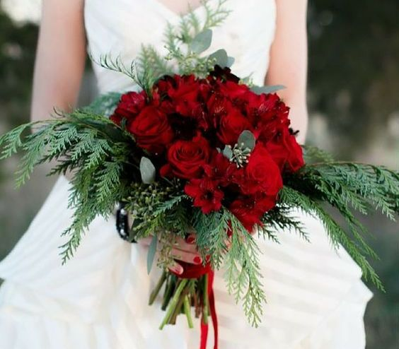 a wedding bouquet of red roses and greenery is a great idea for a winter bride