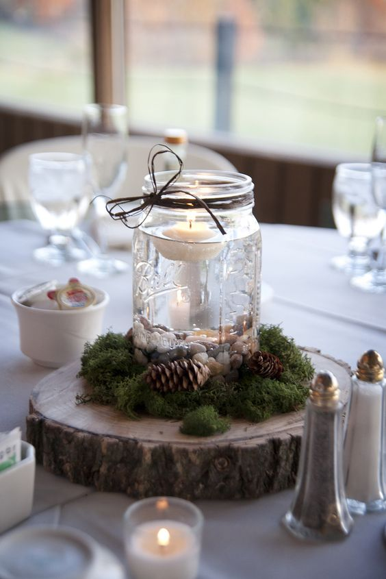 a wood slice with moss, pinecones, a mason jar with pebbles and a floating candle for a rustic wedding