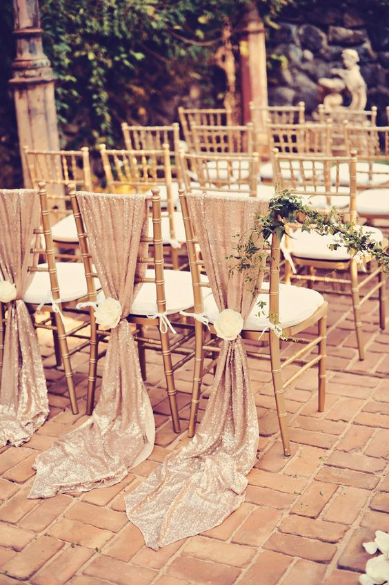 blush sequin chair covers with large white blooms are great to decorate a glam wedding aisle