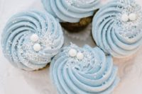 17 cupcakes with blue swirl frosting, edible snow and snowballs are ideal for a winter wedding