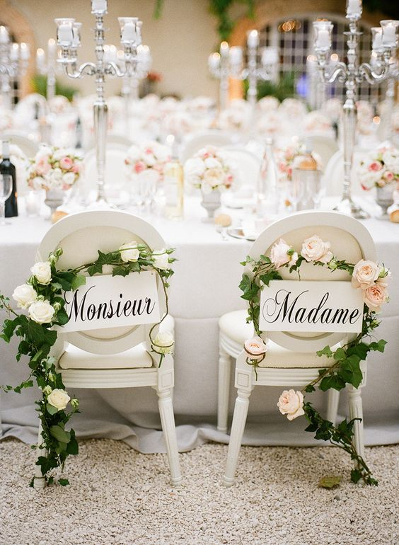 refined white signs with French words, greenery and blush blooms garlands add chic to the chairs