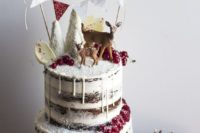 17 woodland-inspired naked wedding cake with white chocolate drip, cranberries, sugar trees, a banner and deer toppers