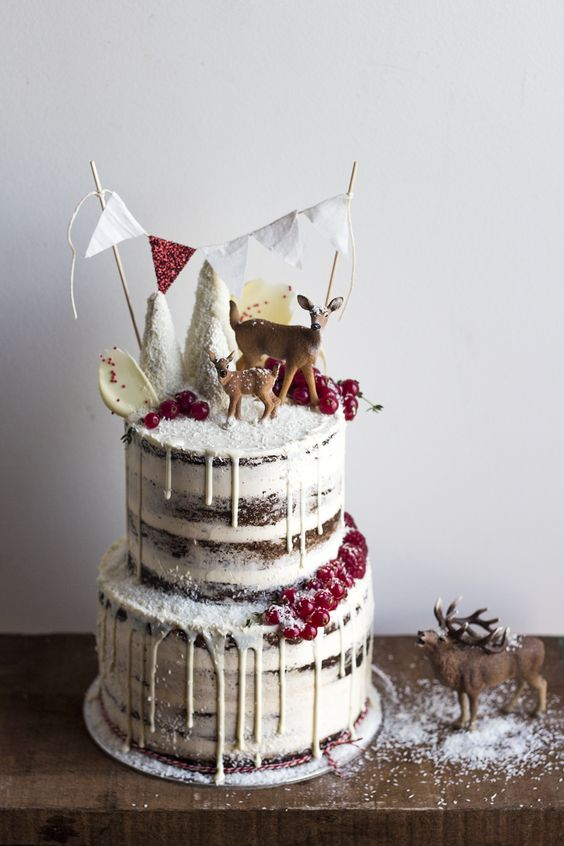 woodland-inspired naked wedding cake with white chocolate drip, cranberries, sugar trees, a banner and deer toppers