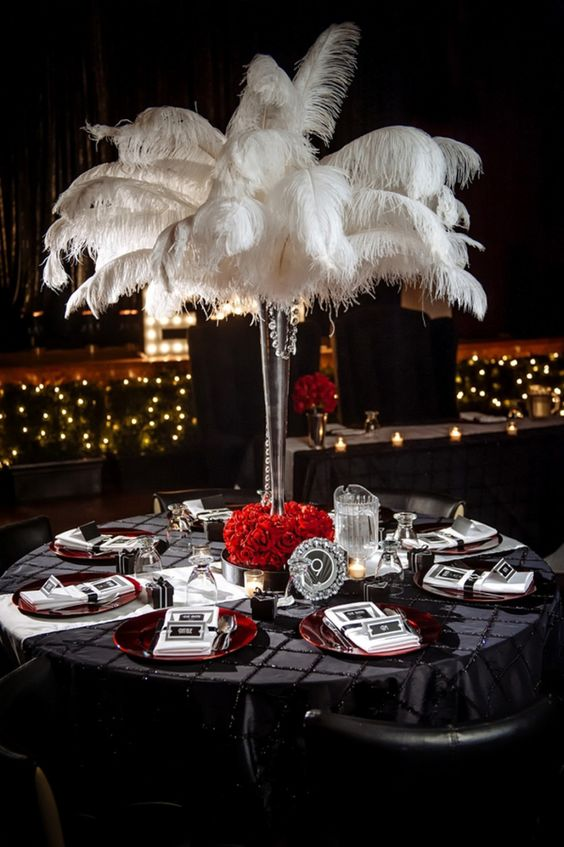 a black, red and whiet tablescape with a feather centerpiece, red roses and chargers and black and white settings