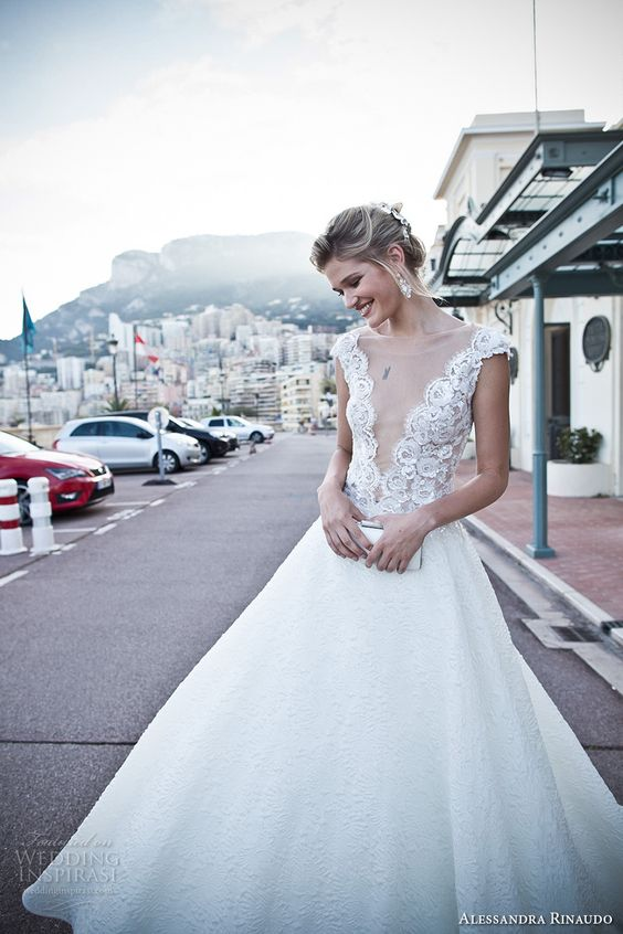 a chic A-line wedding dress with a lace bodice, cap sleeves, a covered plunging neckline and a lace skirt