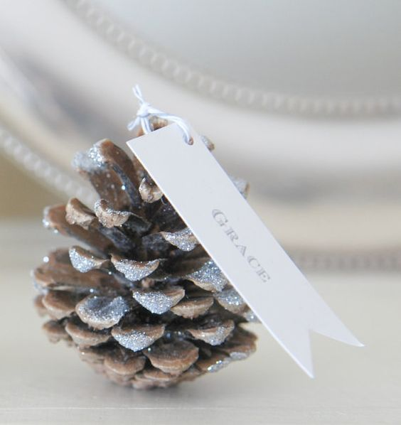 a glittered pinecone as a card holder is a chic idea and such a piece can be DIYed