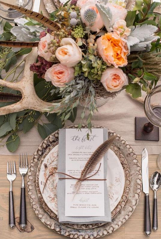 a gorgeous bohow edding centerpiece with lush pastel blooms, greenery, feathers and antlers