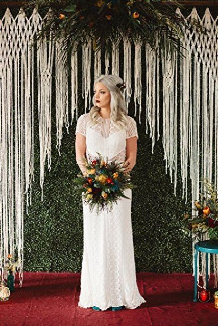 a gorgeous macrame backdrop with greenery and moody blooms all around is great for any boho wedding