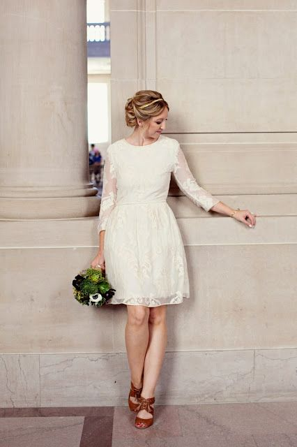 a lace wedding dress with a scoop neckline, long sleeves with brown leather strappy heels for a modest bride
