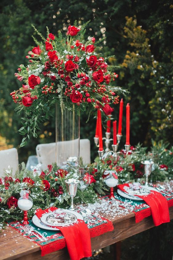 a lush Christmas-inspired tablescape in red and green, with red roses, evergreens, printed napkins and lots of faux snow