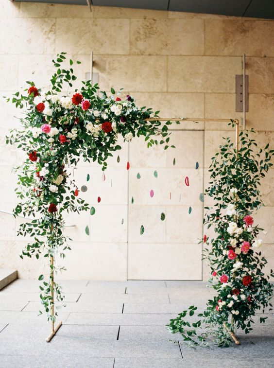 a red and green wedding arch with greenery, blooms and hanging agates for a trendy feel